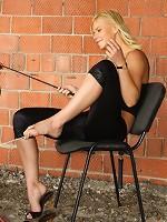 Beautiful mistress Irina humiliating masked slave in front of the brick wall